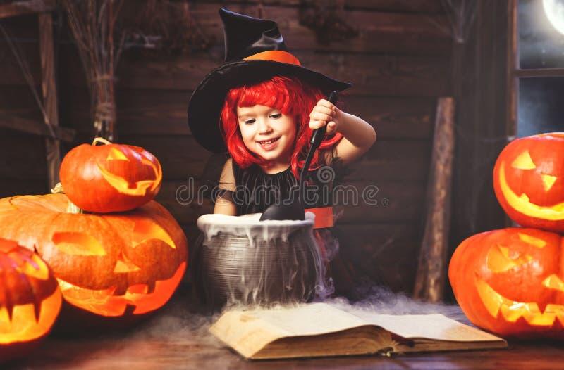 Víspera de Todos los Santos pequeño niño de la bruja que cocina la poción con la calabaza y imagenes de archivo