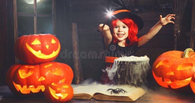 Víspera de Todos los Santos pequeño niño de la bruja que cocina la poción con la calabaza y fotografía de archivo libre de regalías