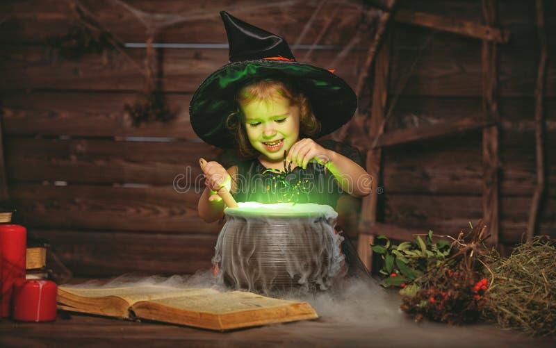 Víspera de Todos los Santos pequeño niño de la bruja que cocina la poción en caldera con imagen de archivo