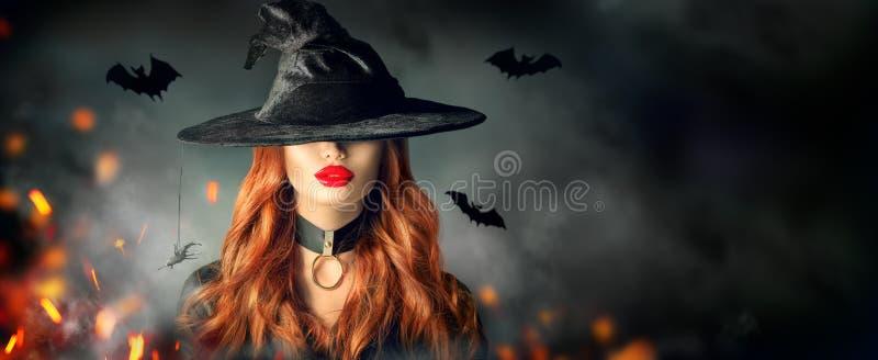 Víspera de Todos los Santos Retrato atractivo de la bruja Mujer hermosa en sombrero de las brujas con el pelo rojo rizado largo fotos de archivo
