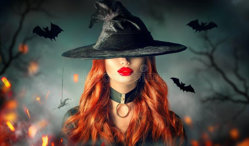 Víspera de Todos los Santos Retrato atractivo de la bruja Mujer hermosa en sombrero de las brujas con el pelo rojo rizado largo imágenes de archivo libres de regalías