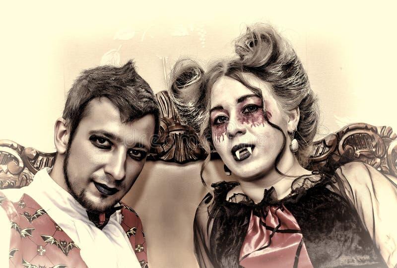 Víspera de Todos los Santos Un par joven de vampiros Equipos de lujo y maquillaje elegante imágenes de archivo libres de regalías