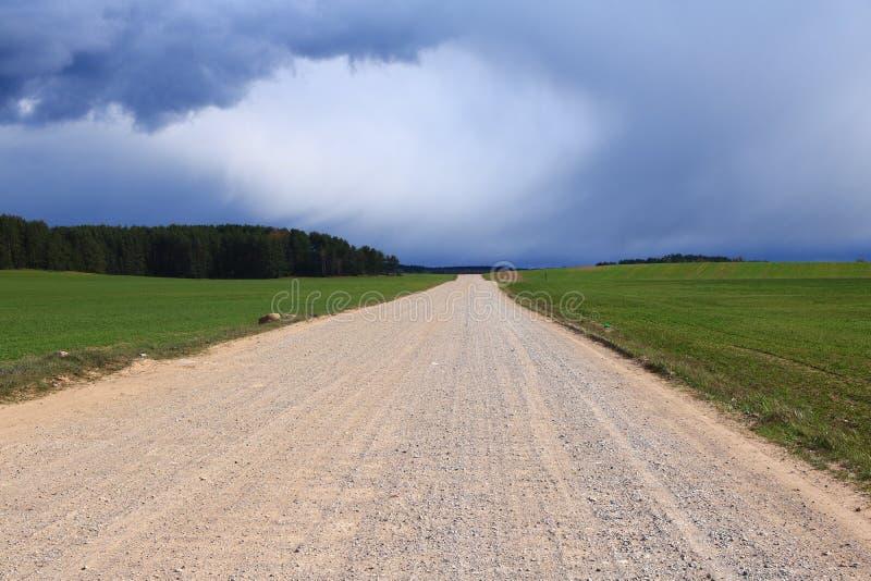 Vóór de regen hingen de donkere wolken over landelijk, gebied, grintweg in Europa, in het midden van een groen gebied stock foto