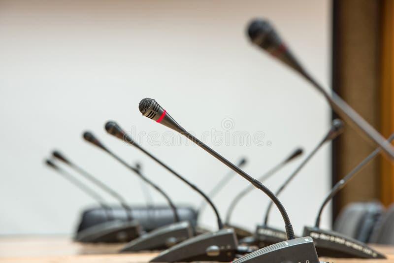 Vóór een conferentie, de microfoons voor lege stoelen Se stock afbeelding