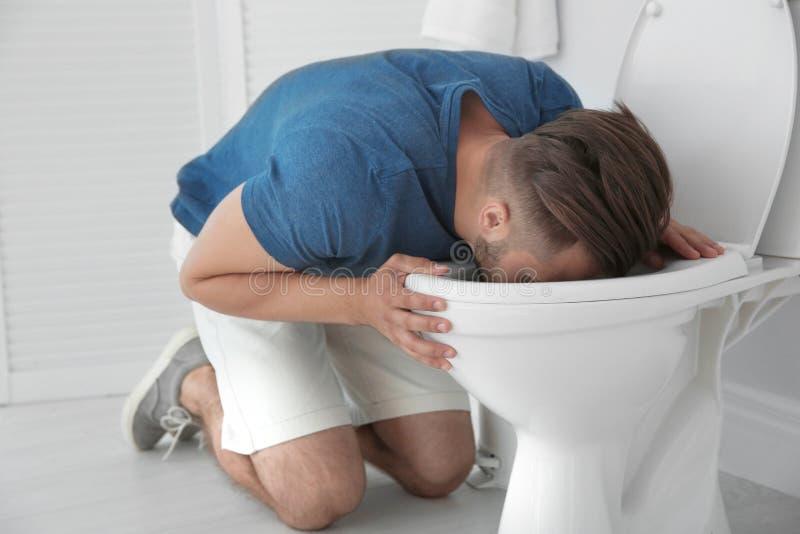 Vômito do homem na bacia de toalete em casa foto de stock royalty free