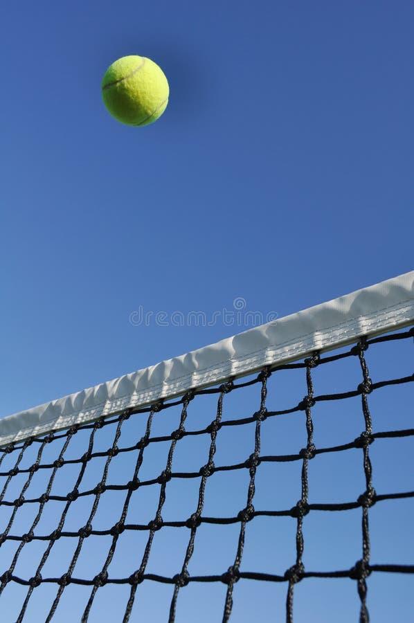 Vôo amarelo da esfera de tênis sobre a rede imagens de stock royalty free