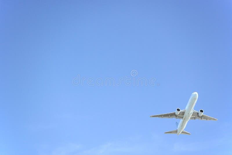 Vôo comercial do avião de encontro ao céu azul fotografia de stock royalty free