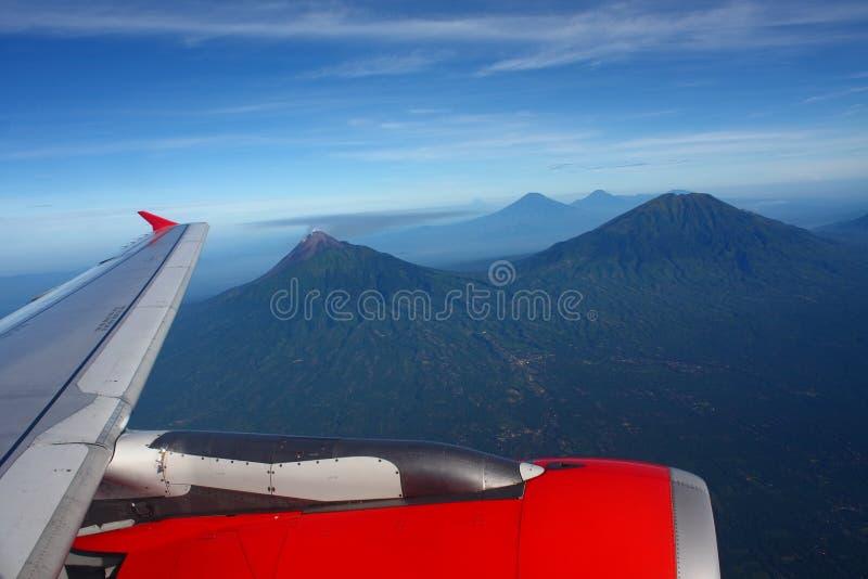 Vôo da asa do avião acima das montanhas foto de stock