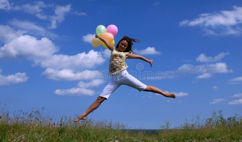 Vôo feliz da mulher com balões coloridos foto de stock royalty free