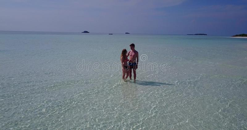 V03981 Aerial flying drone view of Maldives white sandy beach 2 people young couple man woman romantic love on sunny stock photography