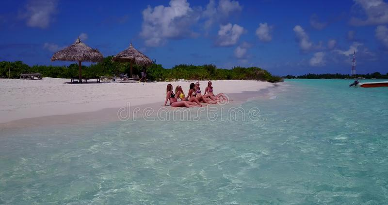 V10810 five 5 beautiful young girls in bikini sunbathing with drone aerial flying view on white sand island sandbank and. Five 5 beautiful young girls in bikini royalty free stock photos