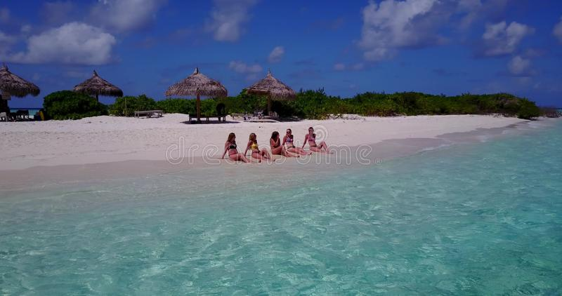 V10809 five 5 beautiful young girls in bikini sunbathing with drone aerial flying view on white sand island sandbank and. Five 5 beautiful young girls in bikini stock images