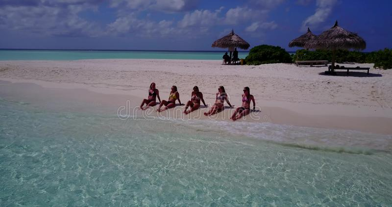 V10802 five 5 beautiful young girls in bikini sunbathing with drone aerial flying view on white sand island sandbank and. Five 5 beautiful young girls in bikini royalty free stock photography