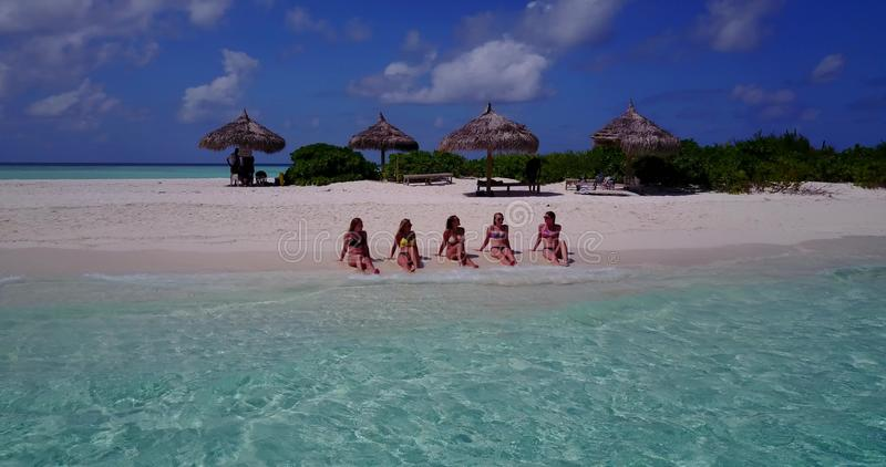 V10808 five 5 beautiful young girls in bikini sunbathing with drone aerial flying view on white sand island sandbank and. Five 5 beautiful young girls in bikini royalty free stock photography