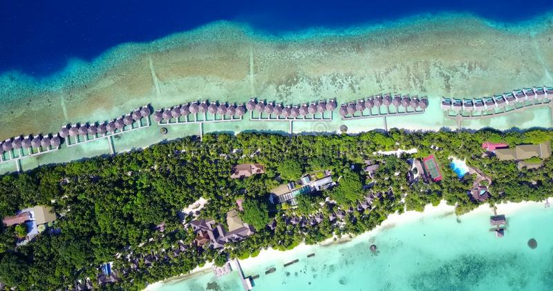 V09493 five 5 star resort water bungalows in Maldives with drone aerial flying view on white sand beach on tropical royalty free stock photography