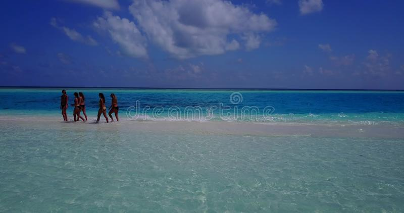 V13819 Five 5 walking beautiful young girls in bikini sunbathing with drone aerial flying view on white sand island. Five 5 walking beautiful young girls in royalty free stock images