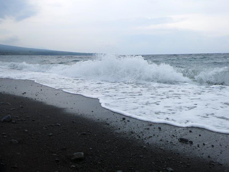 V?g-, br?nning- och havsskum som sl?r den sandiga svarta vulkaniska sandstranden av Bali I Amed ?r havet tyst, men v?gorna runt o arkivfoton