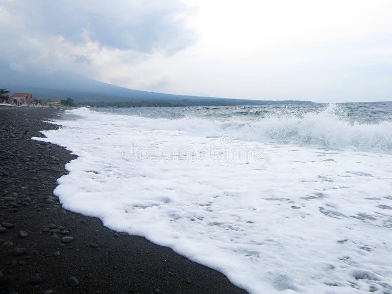 V?g-, br?nning- och havsskum som sl?r den sandiga svarta vulkaniska sandstranden av Bali I Amed ?r havet tyst, men v?gorna runt o royaltyfria foton