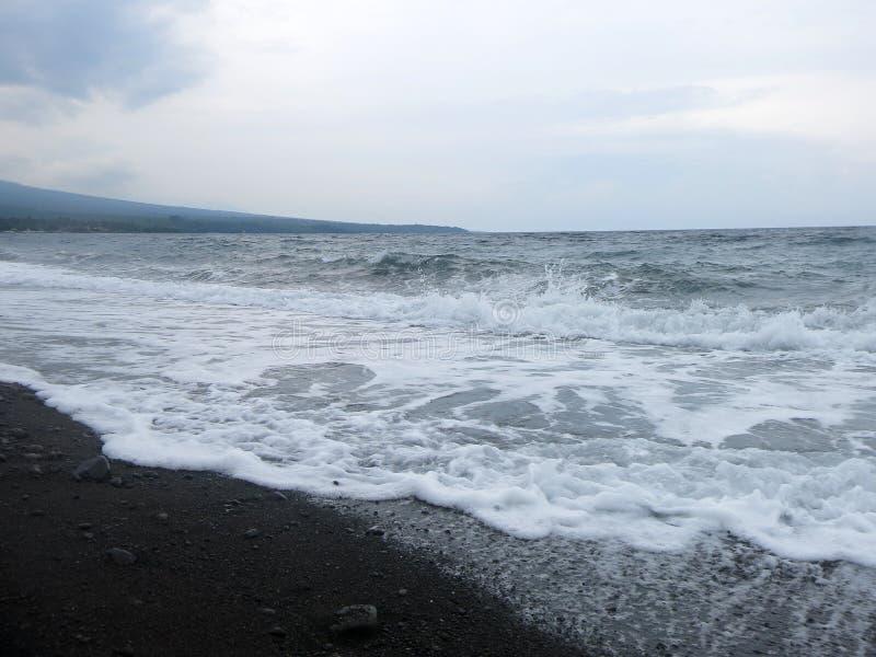 V?g-, br?nning- och havsskum som sl?r den sandiga svarta vulkaniska sandstranden av Bali I Amed ?r havet tyst, men v?gorna runt o royaltyfri fotografi