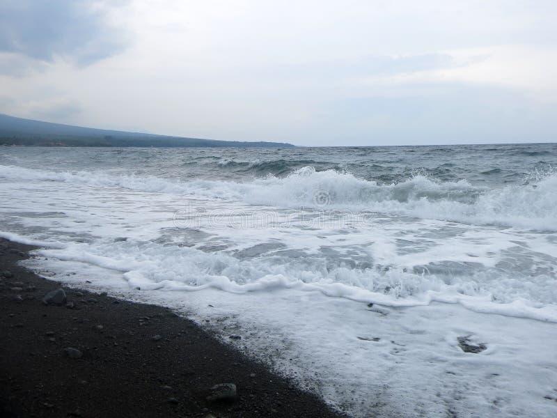 V?g-, br?nning- och havsskum som sl?r den sandiga svarta vulkaniska sandstranden av Bali I Amed ?r havet tyst, men v?gorna runt o arkivbild