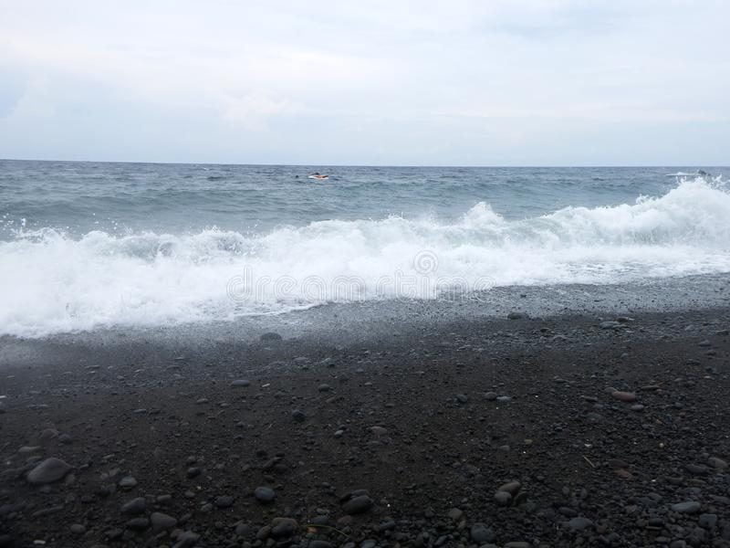 V?g-, br?nning- och havsskum som sl?r den sandiga svarta vulkaniska sandstranden av Bali I Amed ?r havet tyst, men v?gorna runt o arkivbilder