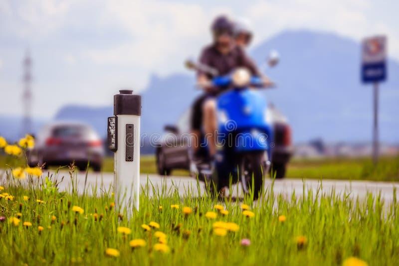V?g i sommaren: par p? en motorcykel, blommor och ett gr?nt gr?s fotografering för bildbyråer