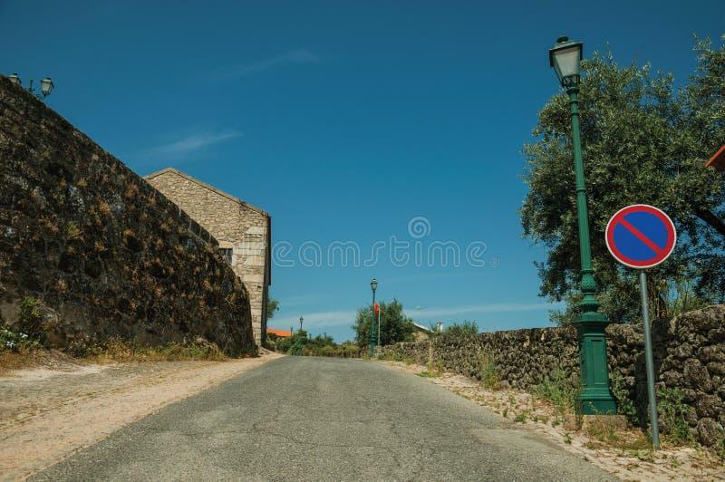 V?g med den ljusa stolpen och INGET PARKERA trafiktecken p? Monsanto royaltyfri foto