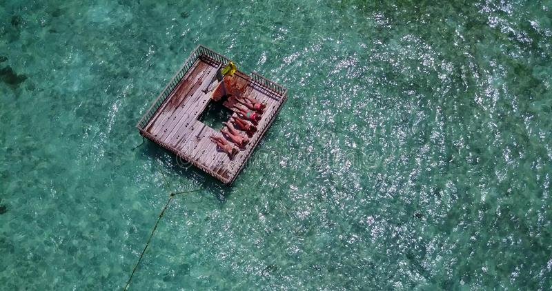 V09156 group of young beautiful girls sunbathing on pontoon with drone aerial flying view in aqua blue clear sea water. Group of young beautiful girls sunbathing stock image