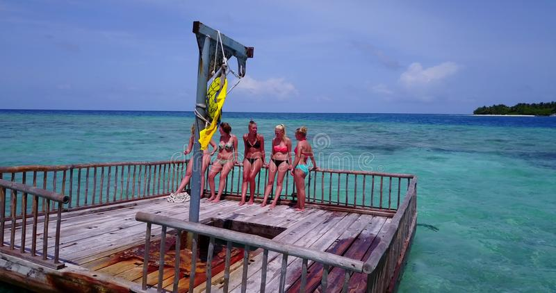 V09246 group of young beautiful girls sunbathing on pontoon with drone aerial flying view in aqua blue clear sea water. Group of young beautiful girls sunbathing royalty free stock photos