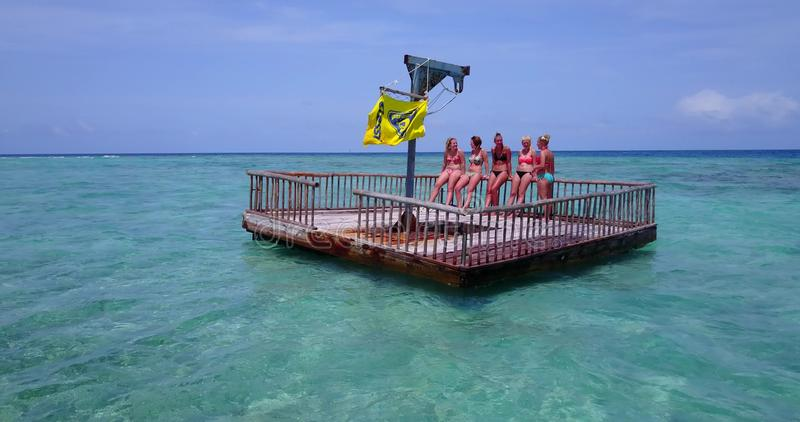 V09247 group of young beautiful girls sunbathing on pontoon with drone aerial flying view in aqua blue clear sea water. Group of young beautiful girls sunbathing stock image