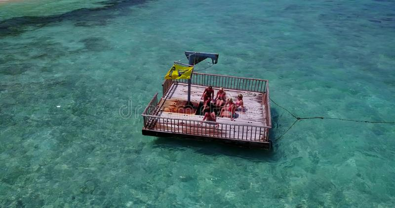 V09174 group of young beautiful girls sunbathing on pontoon with drone aerial flying view in aqua blue clear sea water. Group of young beautiful girls sunbathing royalty free stock photos