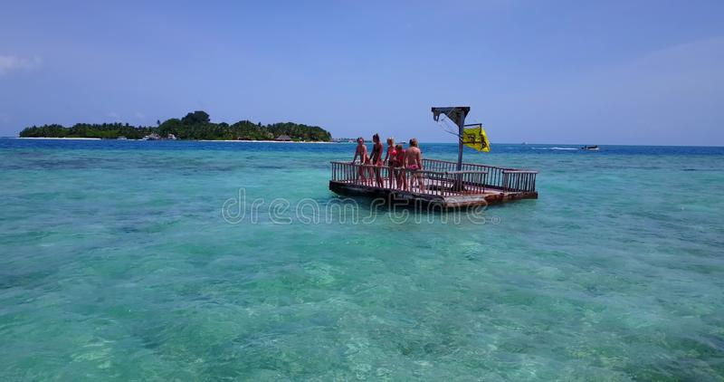 V09228 group of young beautiful girls sunbathing on pontoon with drone aerial flying view in aqua blue clear sea water. Group of young beautiful girls sunbathing stock photography