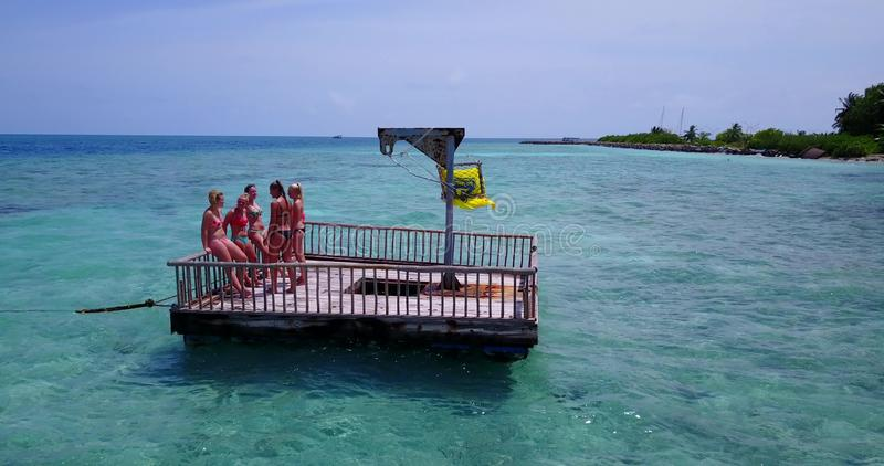 V09195 group of young beautiful girls sunbathing on pontoon with drone aerial flying view in aqua blue clear sea water. Group of young beautiful girls sunbathing stock images