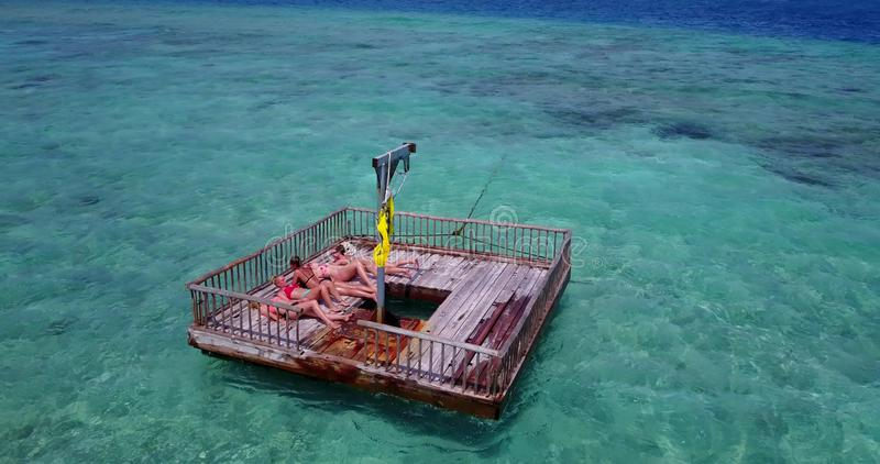 V09160 group of young beautiful girls sunbathing on pontoon with drone aerial flying view in aqua blue clear sea water. Group of young beautiful girls sunbathing stock photo