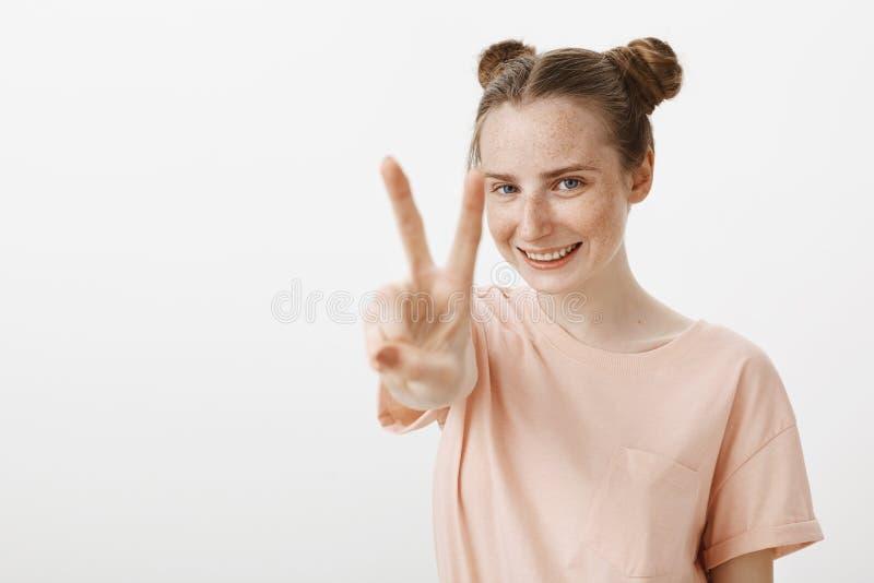 V jest dla zwycięstwa Optymistycznie śliczny młody żeński uczeń w różowej koszulce z pięknymi naturalnymi piegami i niebieskimi o zdjęcie royalty free