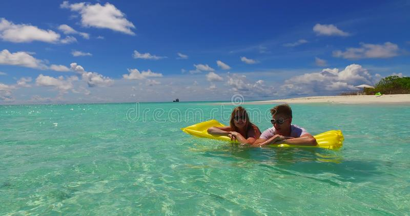 V07265 4k Maldives white sandy beach 2 people young couple man woman floating on airbed inflatable mattress swimming stock photo