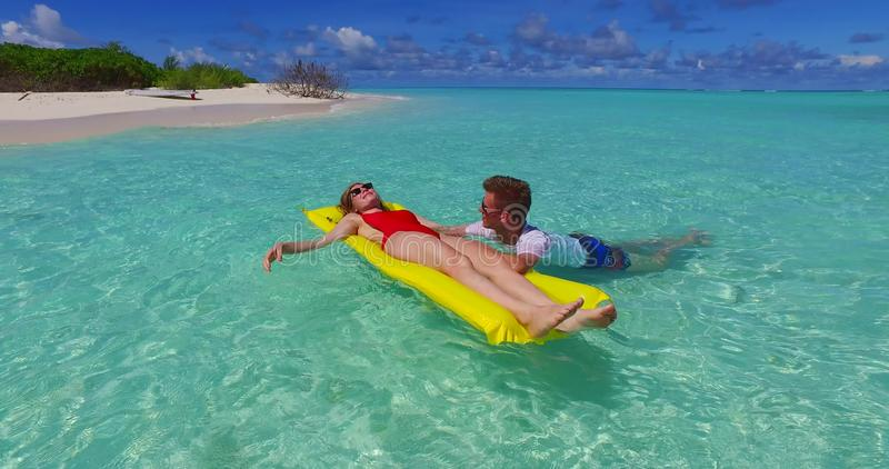 V07268 4k Maldives white sandy beach 2 people young couple man woman floating on airbed inflatable mattress swimming stock photo