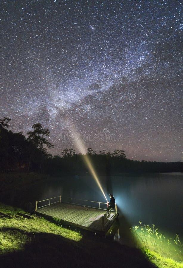 V?a l?ctea Cielo nocturno y silueta de un hombre que se sienta foto de archivo libre de regalías