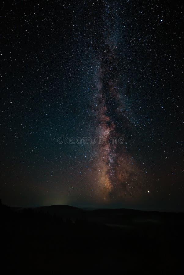 V?a l?ctea y luz rosada en las monta?as Paisaje colorido de la noche Cielo estrellado con las colinas en el verano Universo hermo imágenes de archivo libres de regalías