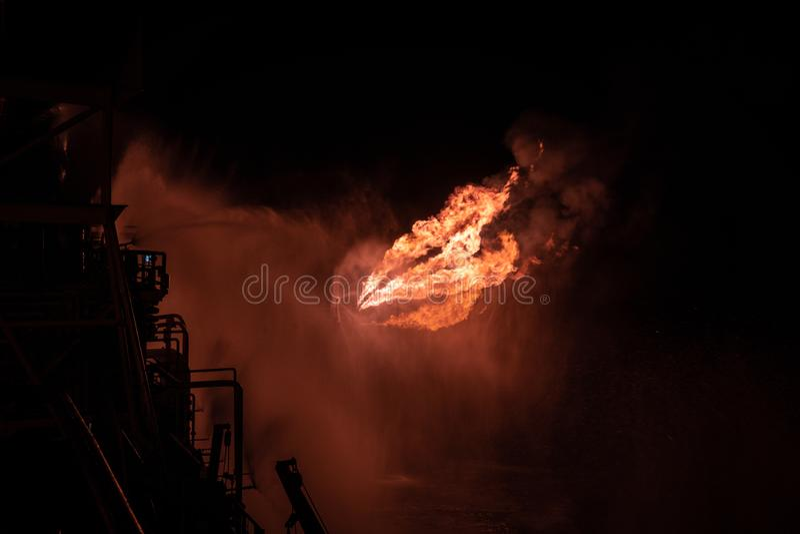 V?l testa blossa f?r operation av en fossila br?nslenborranderigg Br?nnande enorm gasflamma som kontrolleras av st?rtflodsystemet fotografering för bildbyråer