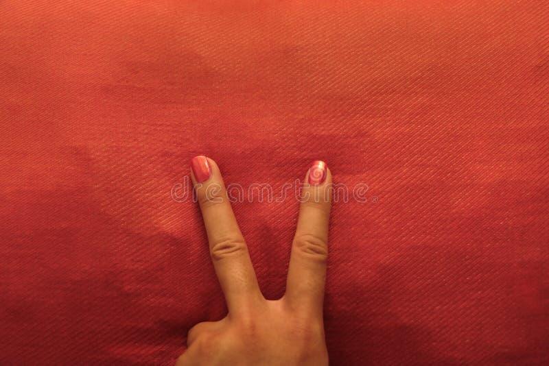 V la main de manucure de signe avec orange vernis à ongles sur l'oreiller assorti - rétro fond image stock
