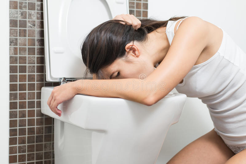 Vômito da mulher na bacia de toalete imagens de stock royalty free