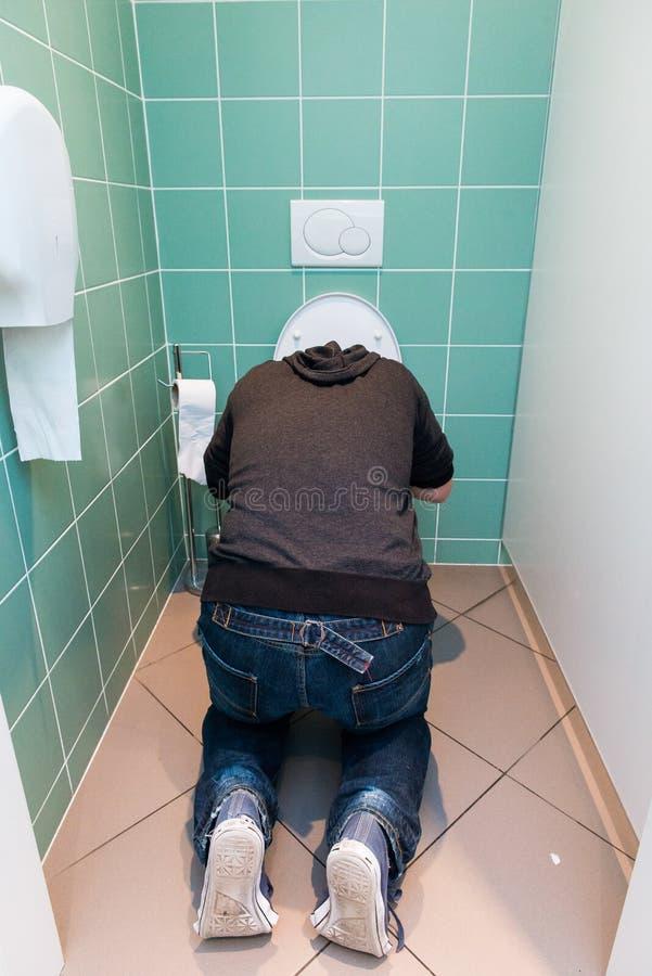 Vômito do homem no toalete imagem de stock royalty free