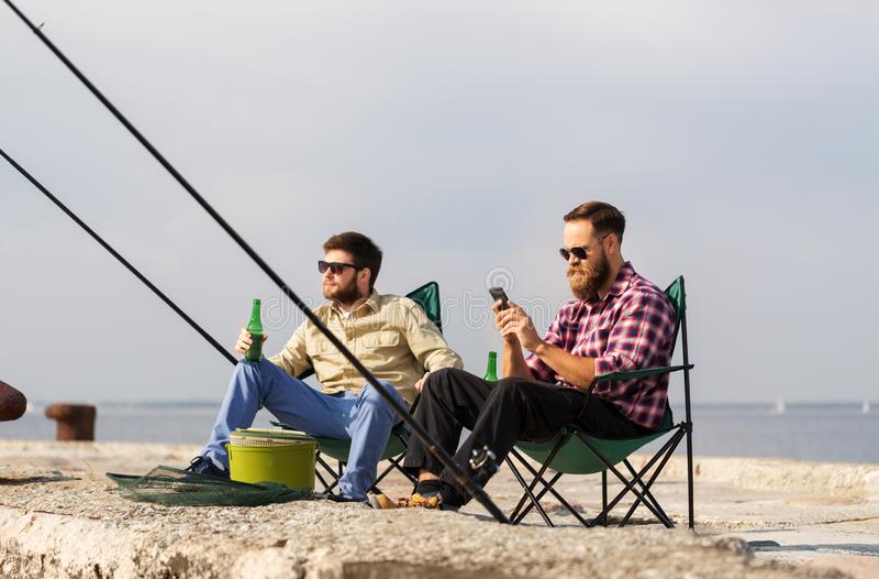 V?nner med smartphonefiske och dricka?l royaltyfri fotografi