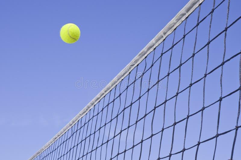 Vôo amarelo da esfera de tênis sobre a rede imagem de stock royalty free