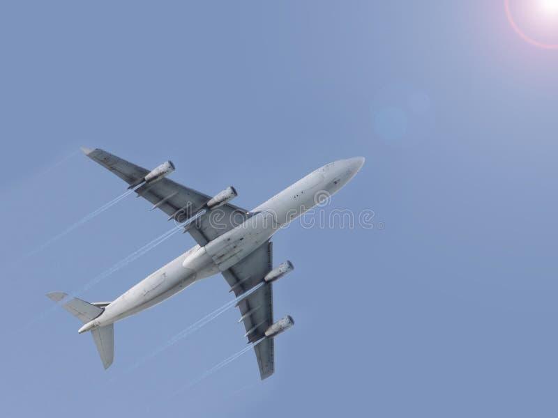 Avião que voa o céu azul    fotografia de stock royalty free