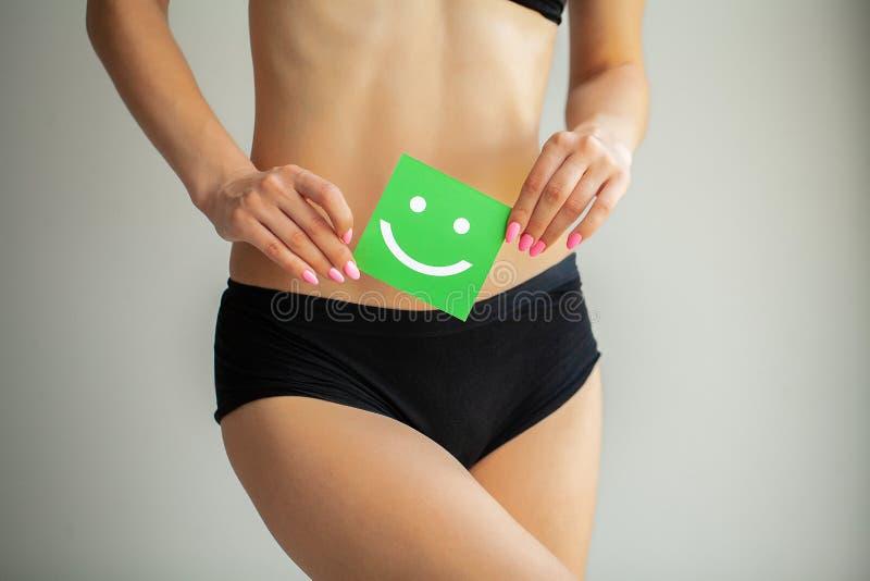 V?rd- kvinnor Closeup av den sunda kvinnlign med den h?rliga f?rdiga slanka kroppen i vita underbyxorar som rymmer det vita korte royaltyfri bild