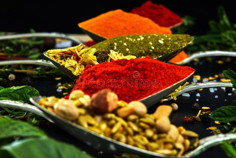 V?rias ervas e especiarias coloridas para cozinhar no fundo escuro imagem de stock