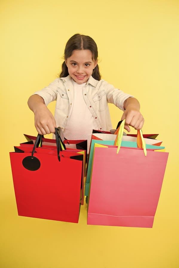 V?rifiez ses paquets d'achats La fille porte le fond jaune de paniers Fille affectueuse des achats Enfant mignon photographie stock libre de droits