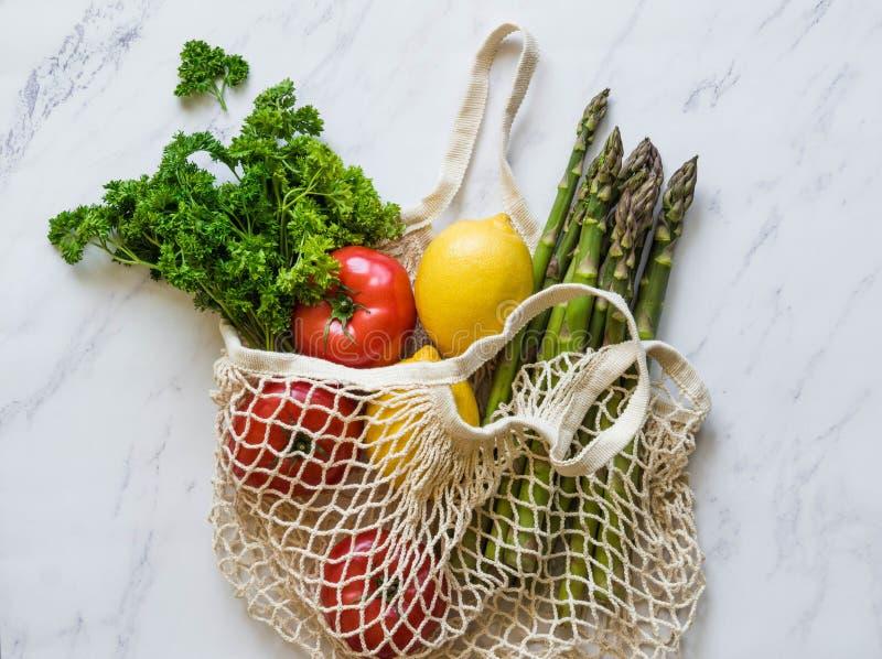 V?rios alimentos frescos - vegetais e frutos no saco eco-amig?vel no fundo de m?rmore branco Refei??o do vegetariano do mercado d foto de stock
